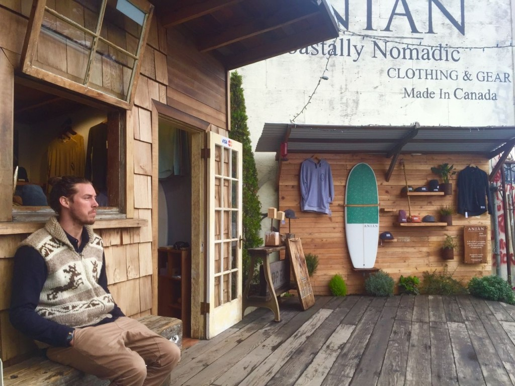 Anian co-owner Paul Long hangs outside his storefront. Inside, he sells clothing designed and made in Canada.